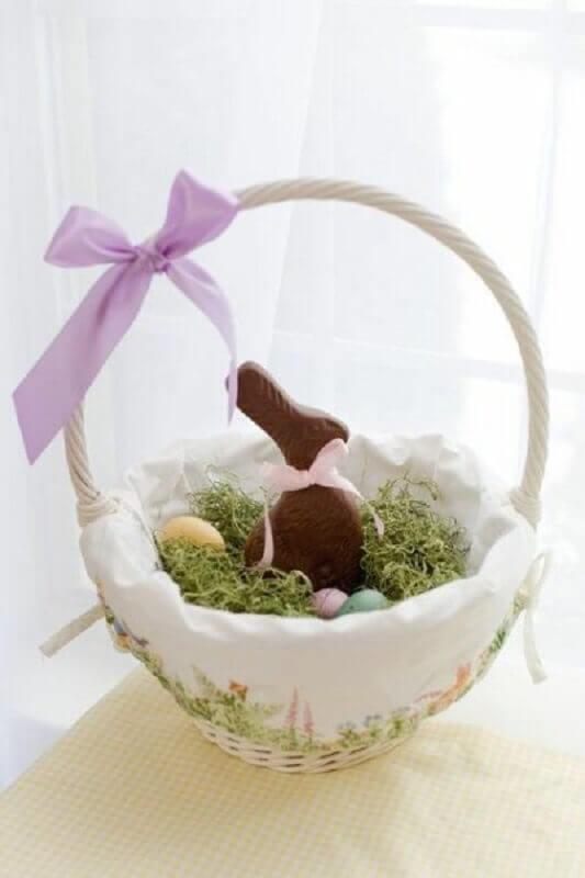 cesta de páscoa com coelhinho de chocolate Foto Pinosy