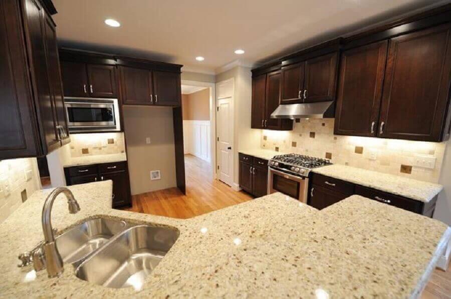 decoração cozinha planejada com armário de madeira escura e granito branco Dallas Foto Istock