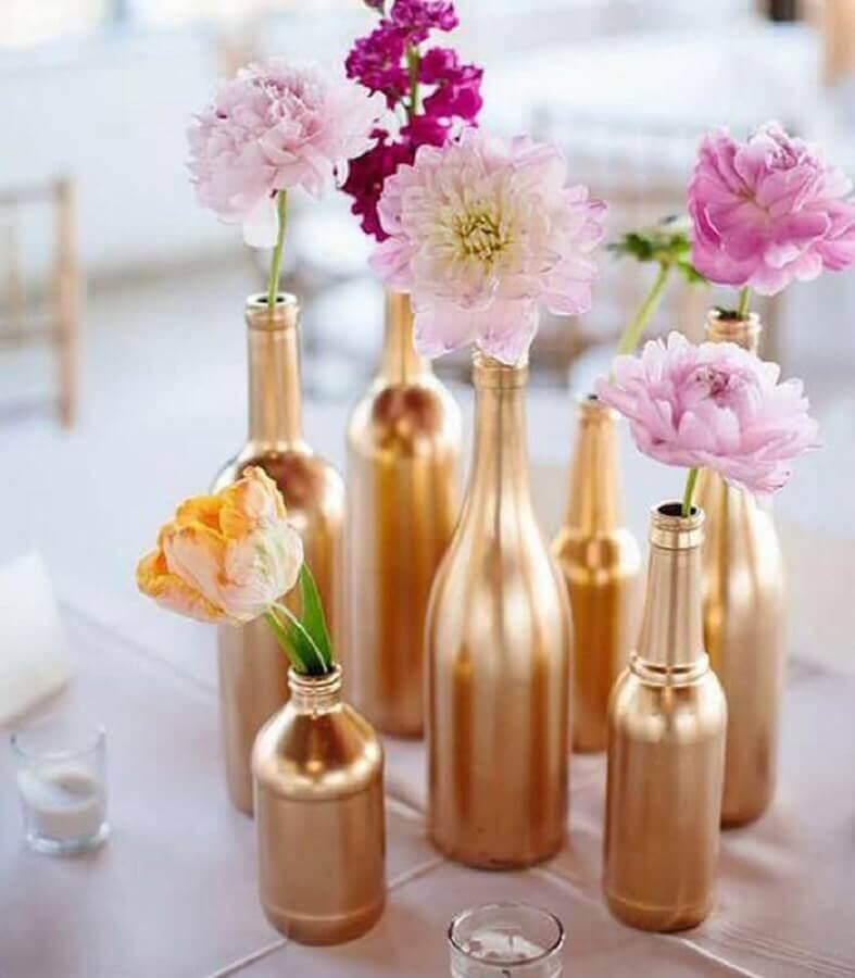 decoração de mesa com garrafas de vidro pintadas de dourado