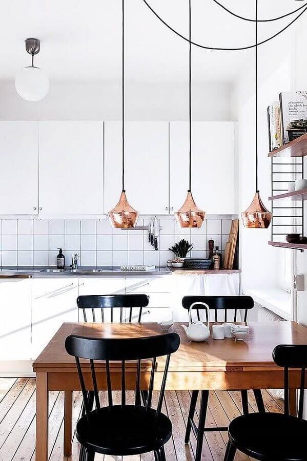 decoração em cobre para cozinha com mesa de madeira cadeiras pretas e luminárias pendentes Foto Dekorama