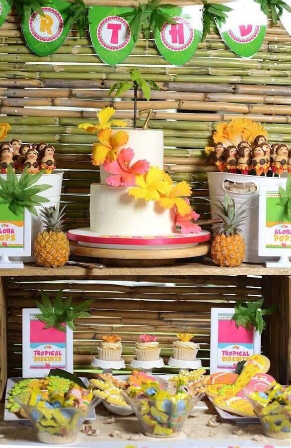 decoração festa havaiana luau com bolo branco dois andares com flores coloridas Foto Assetproject