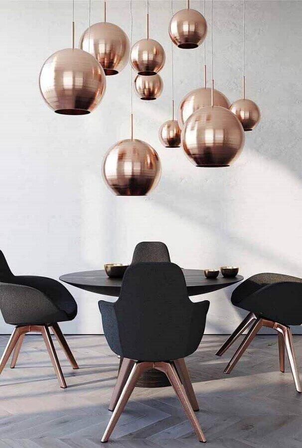 decoração moderna para sala de jantar com mesa redonda cadeiras pretas e luminárias redondas na cor cobre Foto Behance