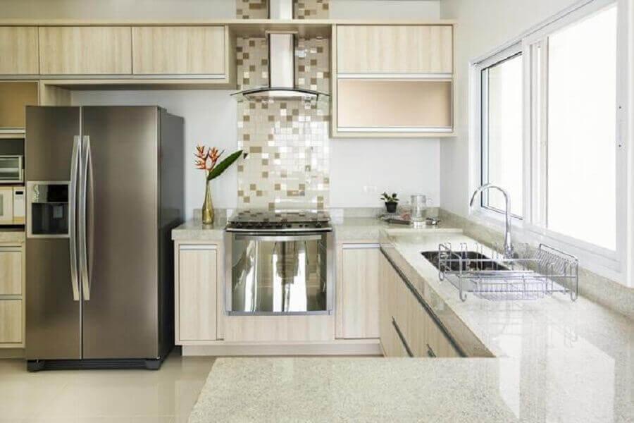 decoração para cozinha planejada com armários em madeira clara e bancada de granito branco Foto Istock