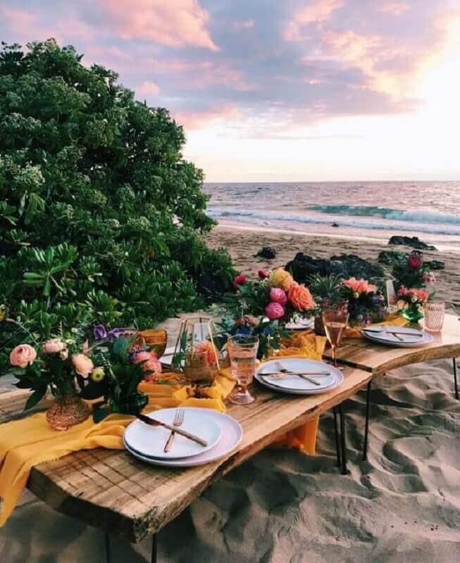 decoração para festa luau na praia com mesa de madeira e arranjo de flores Foto Pinosy