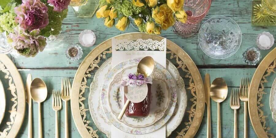 decoração para mesa posta com talheres dourados e mesa rústica de madeira pintada de azul