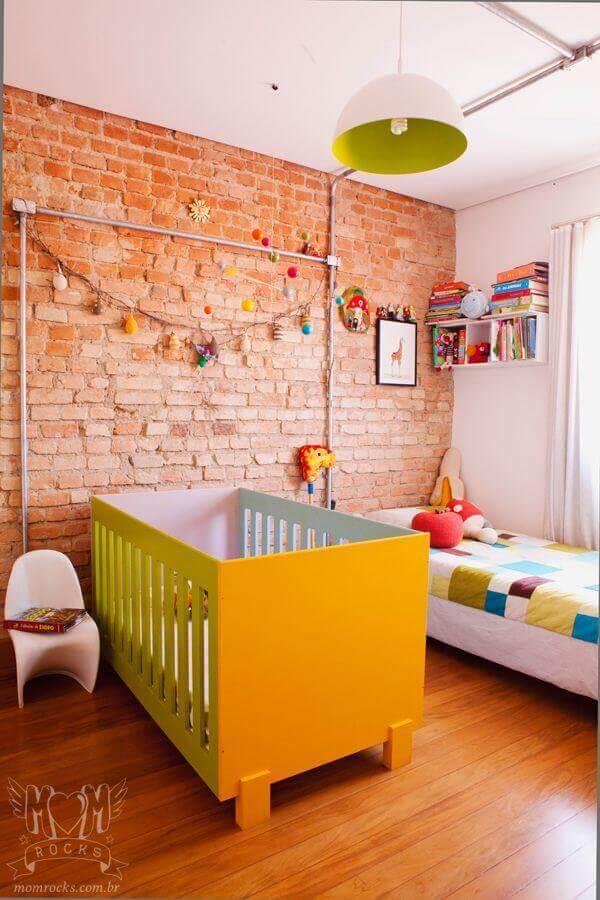 decoração simples com lustre para quarto de bebê com parede de tijolinho Foto Arquitrecos