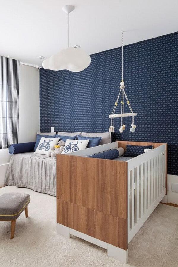 lustre de nuvem para quarto de bebê masculino com papel de parede azul e mobile sobre o berço Foto Aaron Guide