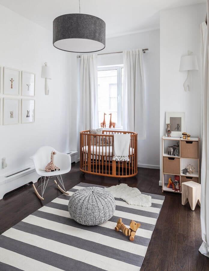 lustre para quarto de bebê decorado em tons de cinza com berço de madeira e tapete listrado  Foto Home BNC