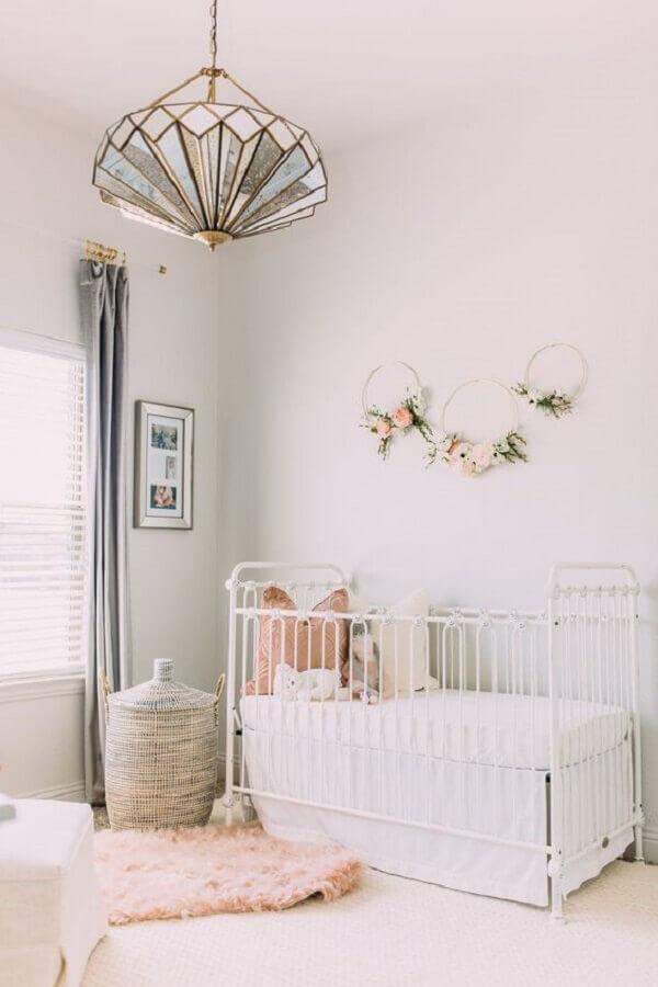 lustre para quarto de bebê feminino decorado com berço branco e argola com arranjos de flores na parede Foto Mabel + Moxie
