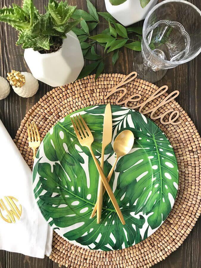 mesa de festa luau decorada com talheres dourados e pratos com estampa de folhagens Foto Pinterest