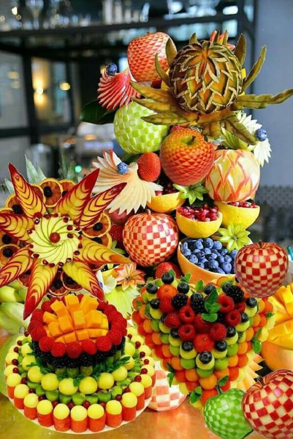 mesa de frutas decoradas com escultura de frutas Foto Pinosy
