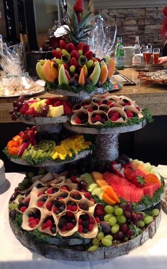 mesa de frutas decoradas com suportes de madeira rústica Foto Pinosy