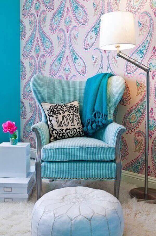 Poltrona na cor azul turquesa contrasta com o papel de parede. Fonte: Pinterest