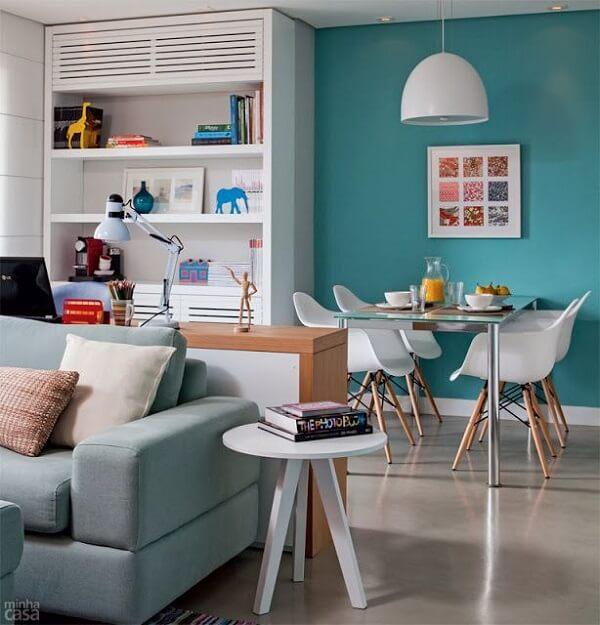 A parede azul turquesa transmite elegância nessa sala de estar pequena