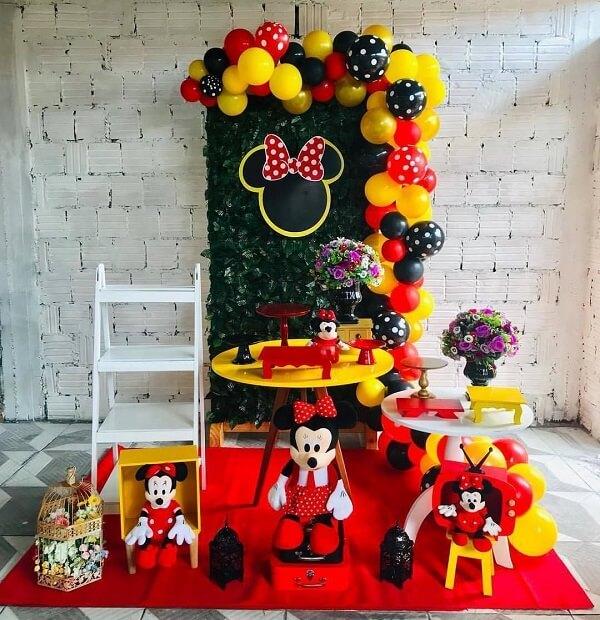 Festa da Minnie simples com estante escada e painel com plantas artificiais