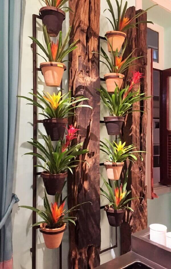 A estrutura rústica do jardim vertical tem em cada vaso uma Bromélia