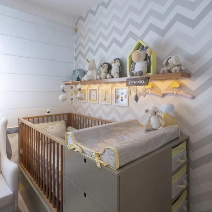 A prateleira para quarto de bebê em madeira se conecta com o acabamento do berço