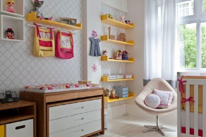A prateleira para quarto de bebê em tom amarelo traz alegria para a decoração