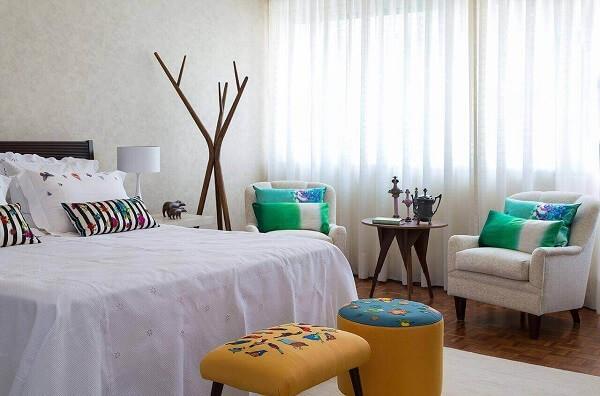 Almofadas coloridas e puff para quarto de casal