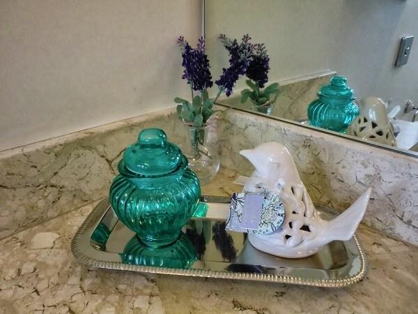 Bandeja decorada com porcelanas utilizada como enfeites para pia de banheiro