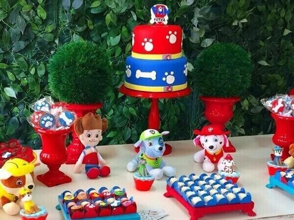 Elementos decorativos na cor vermelha se destacam na mesa do bolo