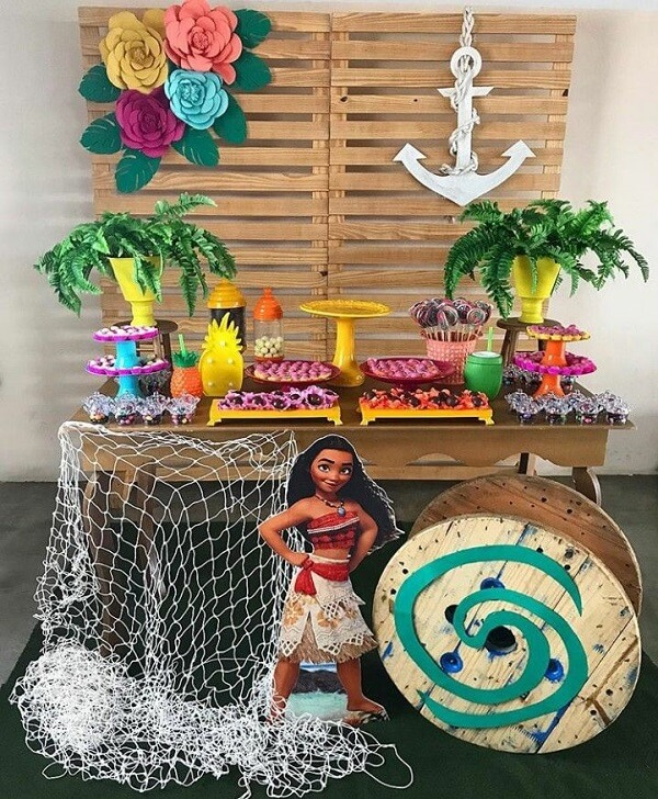 Birthday party with Moana theme has pallet panel and wooden table