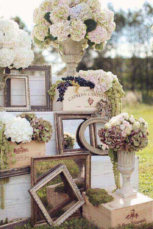 Molduras em madeira e flores em tons sóbrios compõem a decoração vintage