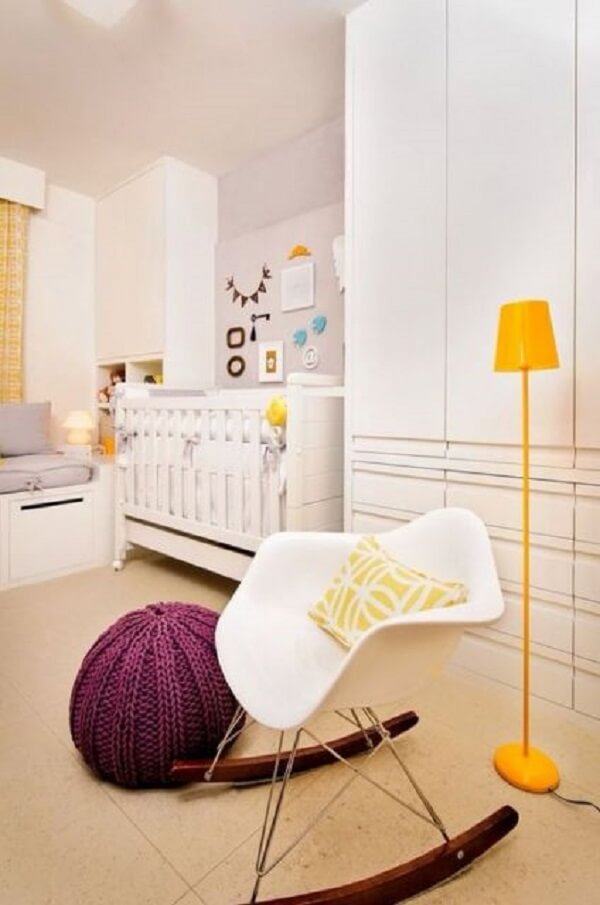 Puff redondo de tricô na cor roxa foi usado ao lado da cadeira branca