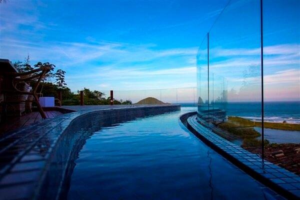 Piscina com borda infinita protegida por placas de vidro