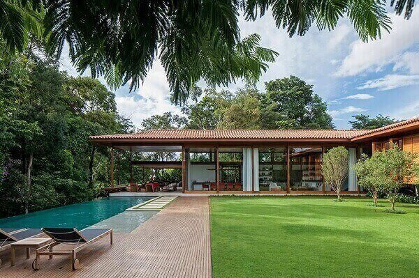 Piscina com borda infinita e deck de madeira interligando os ambientes