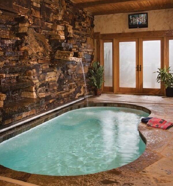 Piscina irregular em alvenaria com parede pedra e cascata