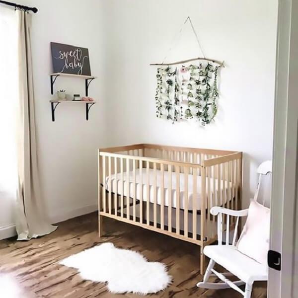 Tapete pequeno e parede com tecido compõem a decoração do quarto de bebê simples