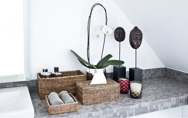 Velas e cestos organizadores e utilizados como enfeites para banheiro pequeno