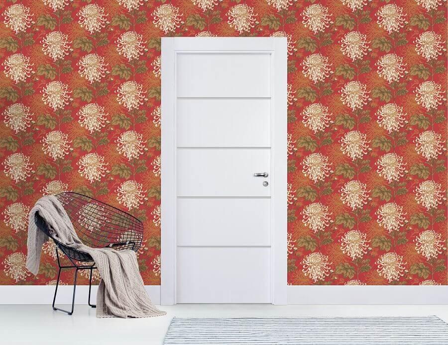 ambiente decorado com porta branca e papel de parede vermelho