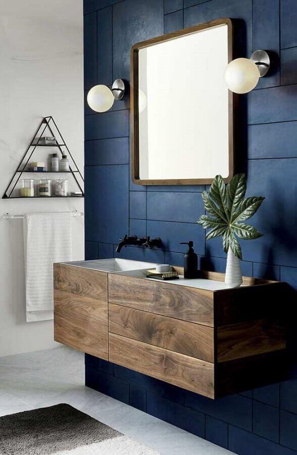 banheiro masculino decorado com revestimento azul escuro e armário de madeira Foto Mauricio Gebara Arquitetura