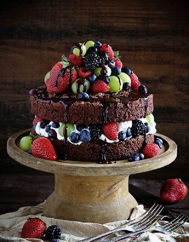 bolo de chocolate decorado simples com muitas frutas e calda Foto Pinosy