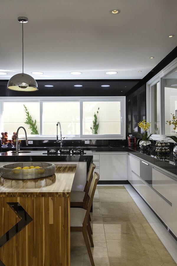 cozinha planejada preta e branca com mesa de madeira Foto Iara Kilaris