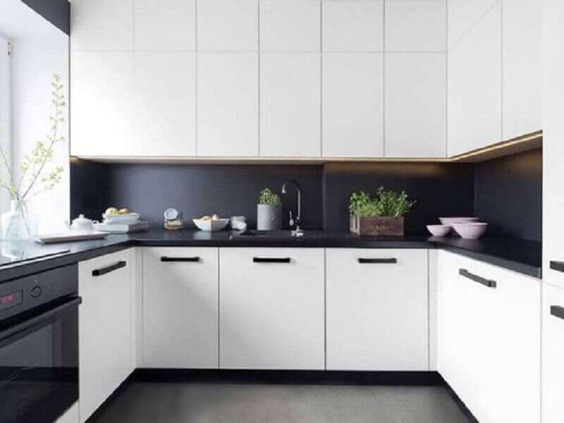 cozinha planejada preta e branca decorada com piso e revestimentos pretos e armários brancos Foto Idea Brasil