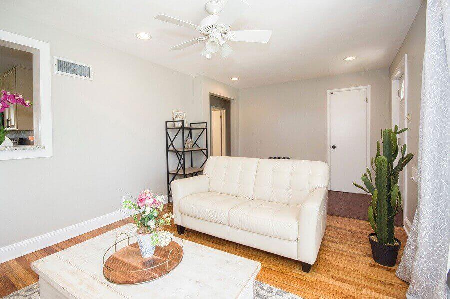 decoração clean para sala de estar com sofá branco e vaso de cactos Foto Pexels