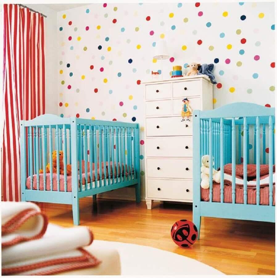 decoração colorida para quarto de bebê gêmeos com papel de parede de bolinhas e berço azul Foto Be Creative