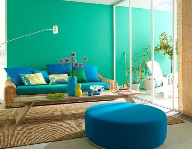 decoração com parede verde água para sala com sofá de vime e puff redondo azul Foto Jaeger Arquitetura