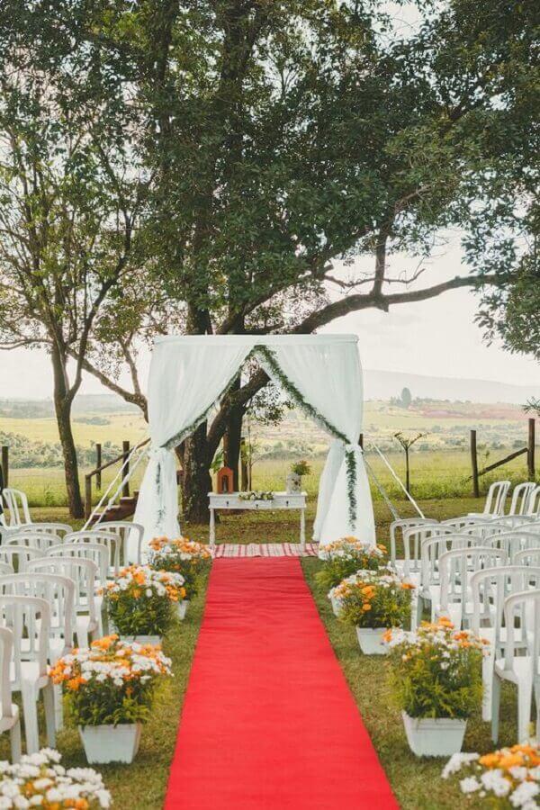 decoração de casamento ao ar livre com vasos de flores brancas e amarelas e tapete vermelho Foto Pinterest