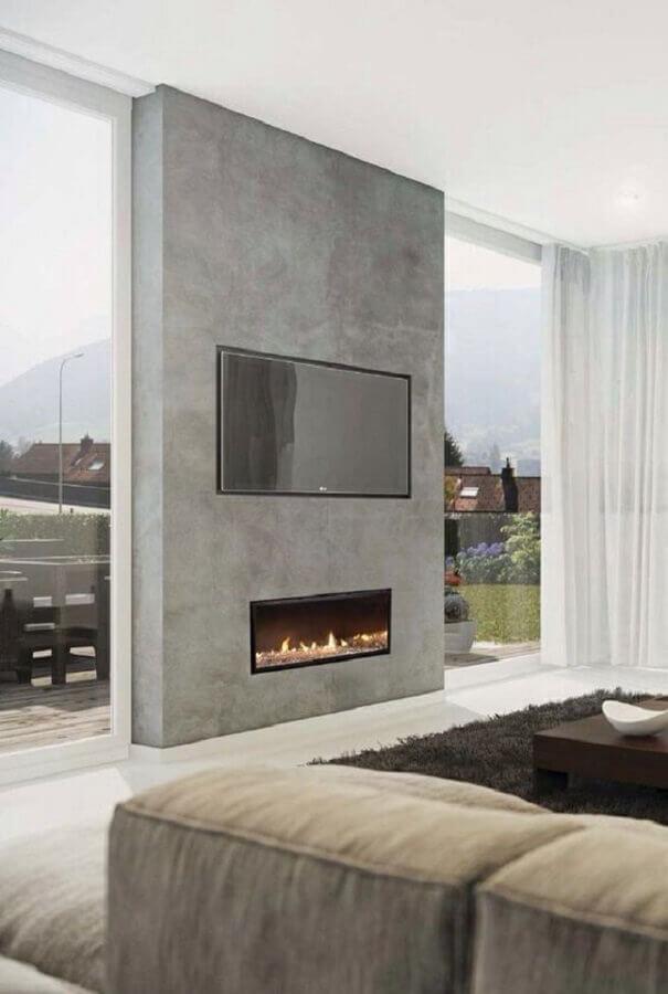 decoração moderna e sofisticada com lareira elétrica embutida em parede de cimento queimado Foto Monta Villa Makers