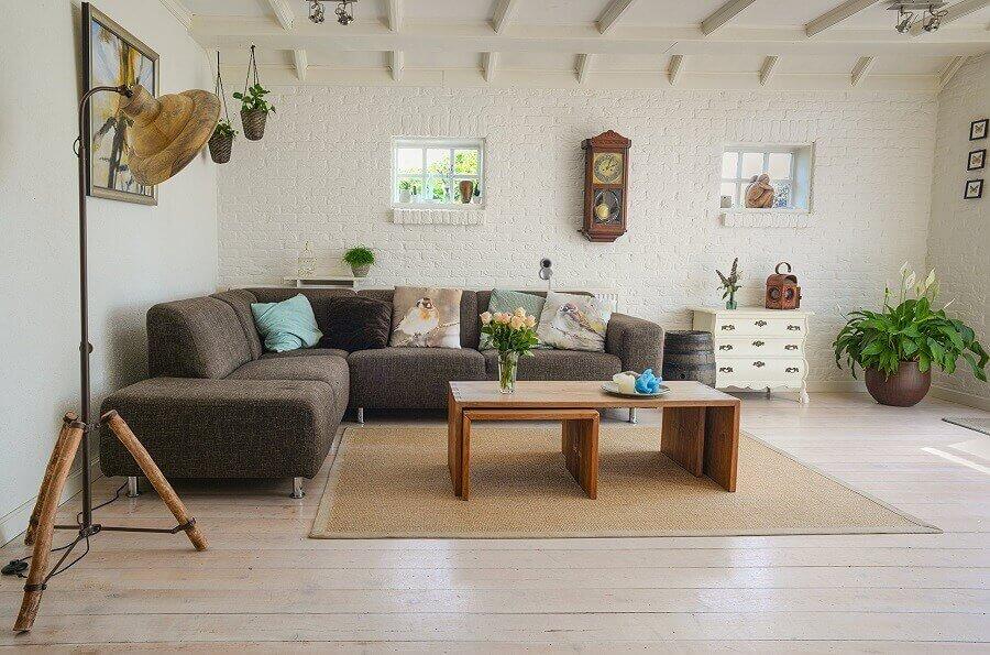 decoração moderna para sala de estar ampla com parede de tijolinho branco e sofá de canto Foto Pexels