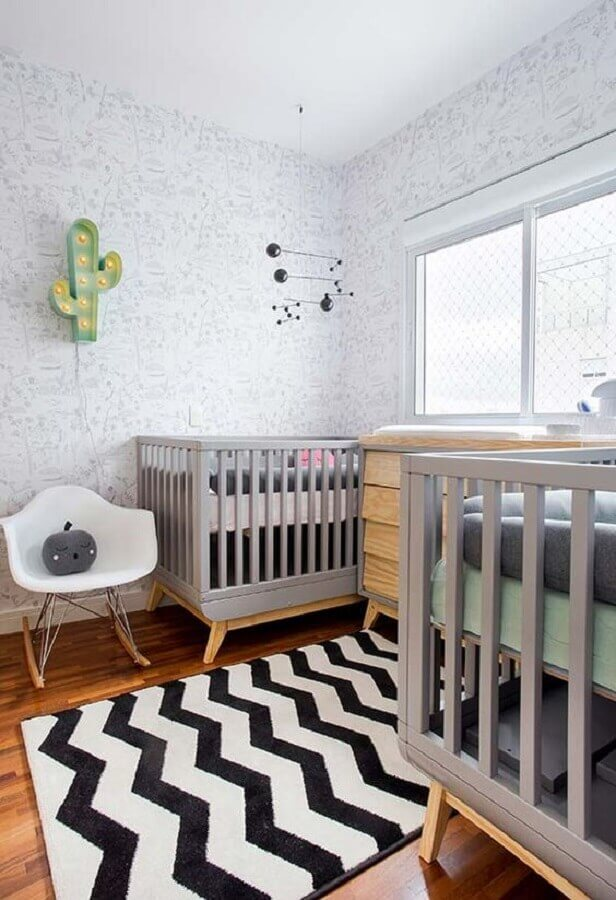 decoração neutra para quarto de bebê gêmeos com berço cinza e tapete preto e branco Foto Pinterest