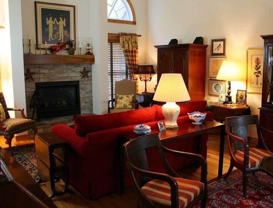 decoração para sala com sofá vermelho e móveis de madeira escura Foto Pexels