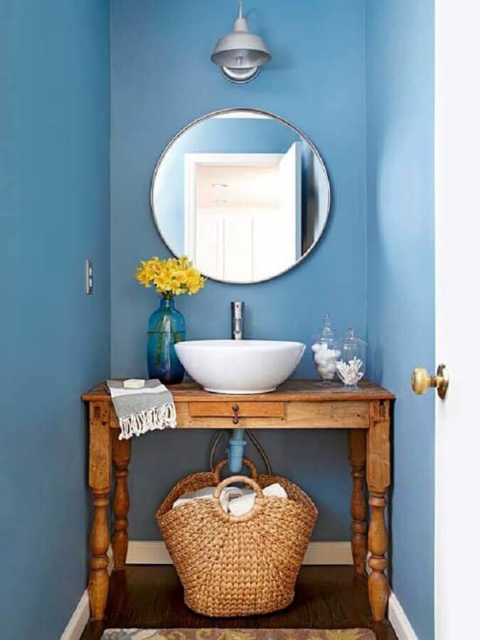 espelho para lavabo pequeno decorado com móvel antigo de madeira e paredes azuis Foto Julie Holloway Studio
