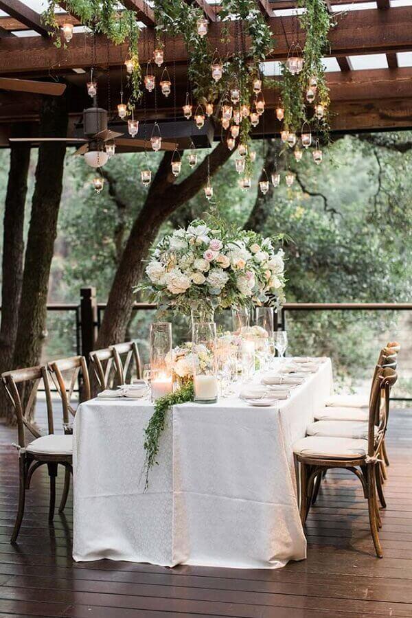 festa de casamento ao ar livre decorado com pequenas velas suspensas e arranjos de rosas Foto MODwedding