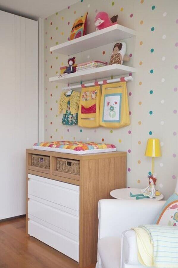 prateleira para quarto de bebê decorado com cômoda de madeira e papel de parede de bolinhas coloridasFoto Vamos Mamães
