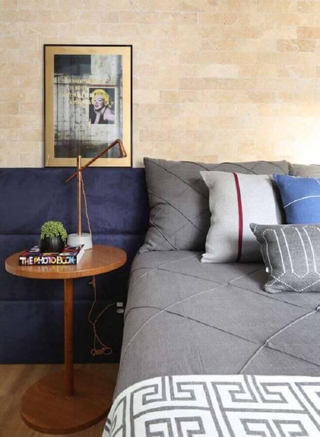 quarto azul decorado com parede de tijolinho e mesa lateral redonda Foto Casa Vogue